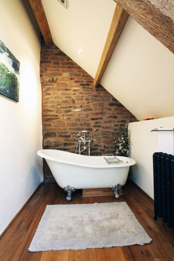 a barn bathroom with white walls and a ceiling, wooden beams, a stone wall, a clawfoot tub and an artwork