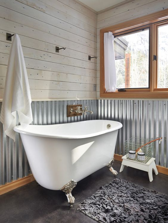 a barn bathroom with whitewashed wooden planks, corrugated steel on the walls, a clawfoot tub, a large window and a fluffy rug