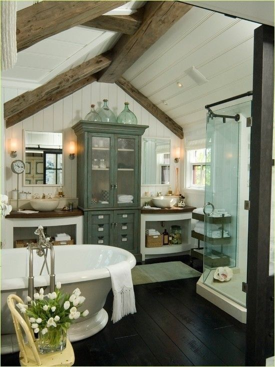 a barn bathtub in white, with stained wooden beams, an elegant free-standing tub, vintage furniture and a glass enclosed shower