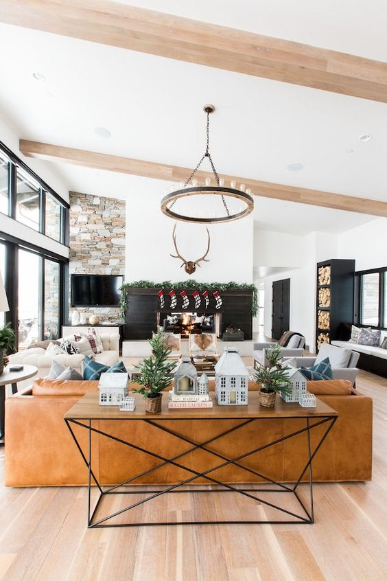 a barn living room with a fireplace clad with black planks, a TV on a stone wall, a leather sofa and neutral seating furniture, a round chandelier