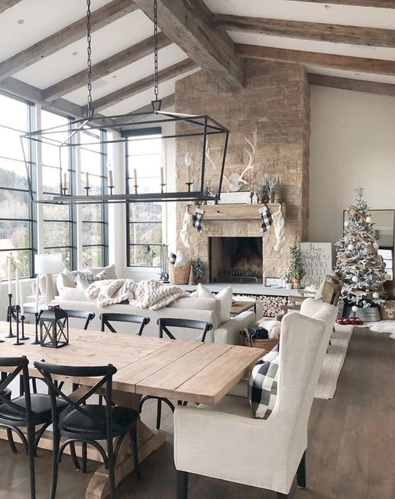 a barn living room with a glazed wall, a fireplace clad with stone, wooden beams on the ceiling, neutral seating furniture and pendant lamps