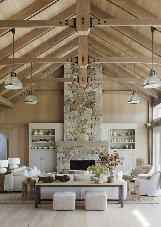 a barn living room with stained walls and a ceiling, with wooden beams, a fireplace clad with stone, neutral seating furniture and built-in storage units