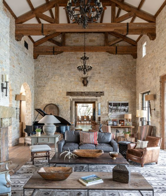a barn living room with stone walls, wooden beams on the ceiling, brown, grey and white furniture, a piano, refined metal chandeliers and low coffee tables