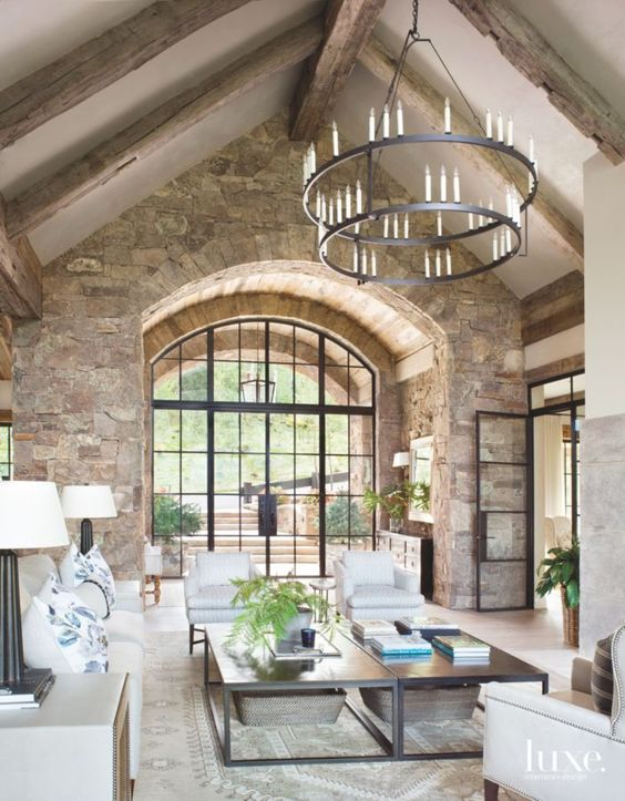 a barn living room with stone walls, wooden beams on the ceiling, neutral seating furniture, low coffee tables and a metal chandelier