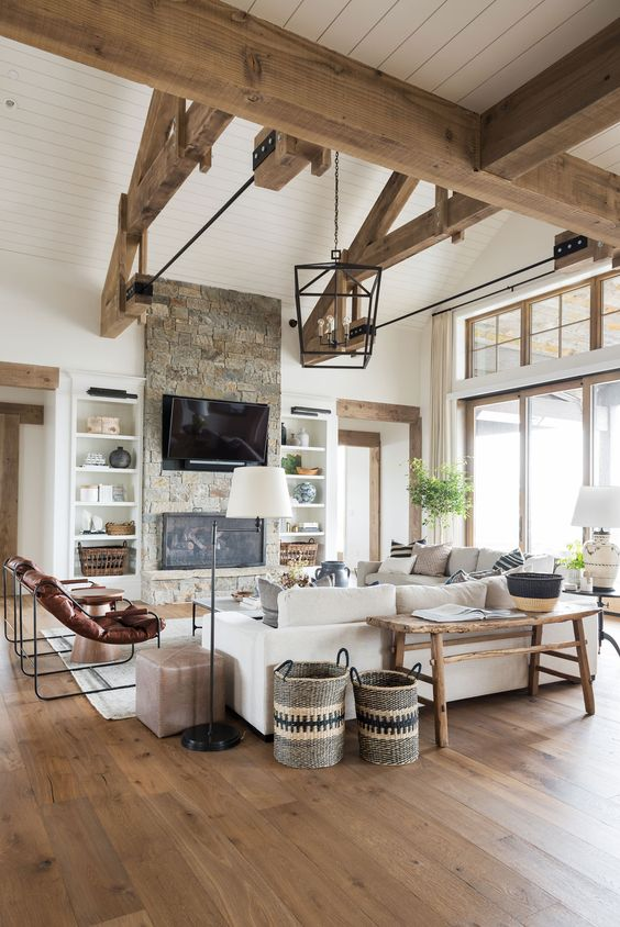 a barn living room with woodenn beams, white planked walls, a fireplace clad with stone, neutral seating furniture, leather chairs and baskets
