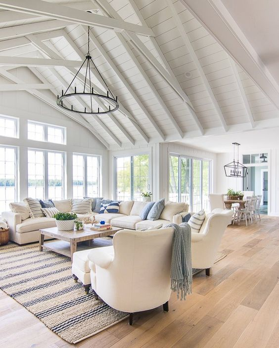 a beach barn living room in white, with woodne beams, white seatign furniture, printed textiles, a metal round chandelier, lovely views of the beach