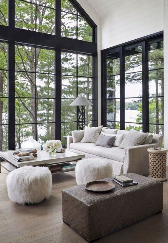 a beautiful barn living room with double-height windows, neutral furniture and a brown ottoman, faux fur stools is amazing