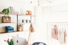 a beautiful feminine closet with open shelves, an acrylic desk, a blue chair and touches of pink is a lovely idea