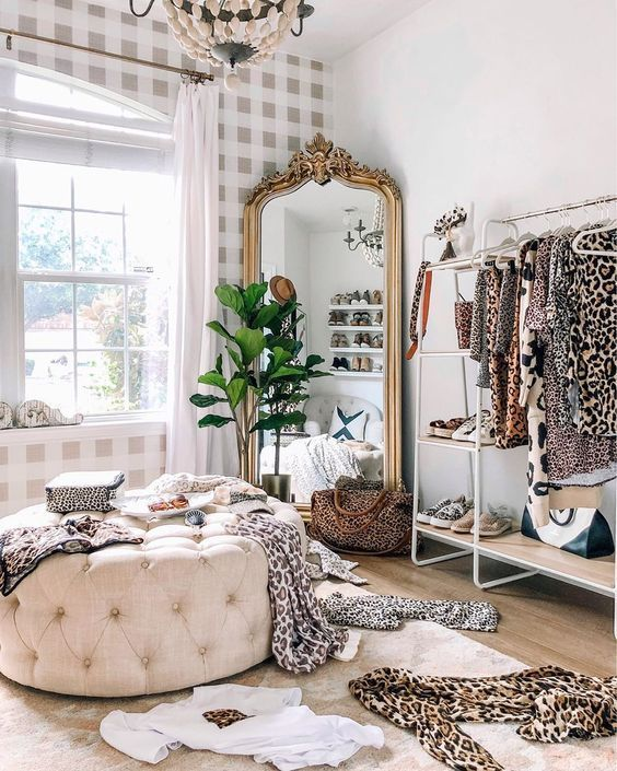 a bold feminine closet with an open storage unit, a shoe shelf, a mirror in an ornated frame, a neutral tufted pouf and a potted plant