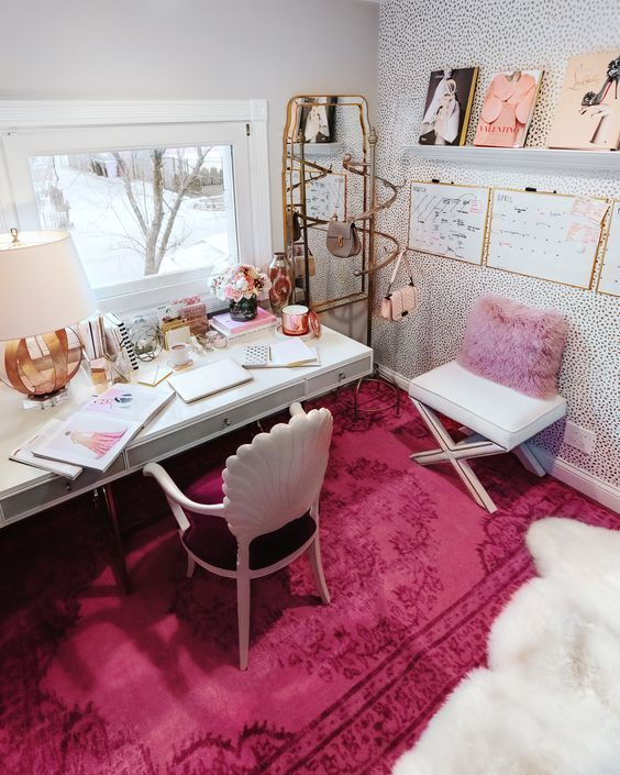 a bold feminine home office with a refined plum chair, a hot pink rug and pillow, a cool gallery wall and touches of gold