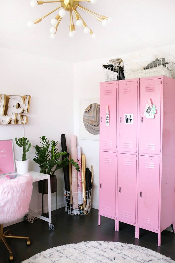 a bold glam feminine home office with pink furniture and art, a gold burst chandelier and potted plants