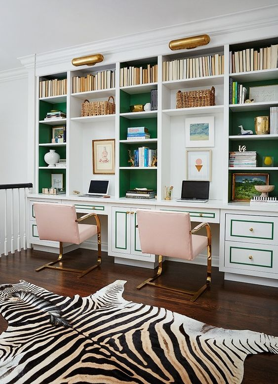 a bright and catchy home office with a large storage unit with emerald backing, blush chairs and gold touches