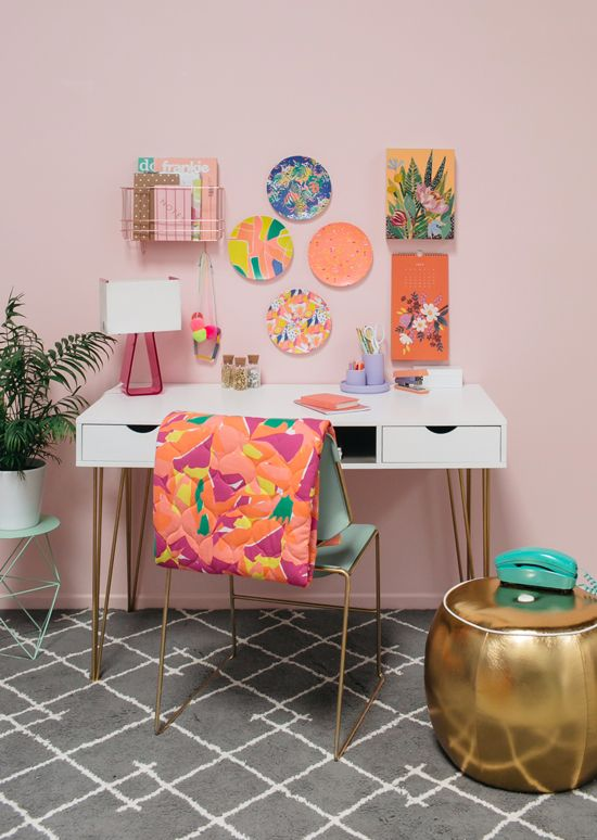 a bright feminine home office with a blush wall, a bright gallery wall, a colorful chair and gold touches
