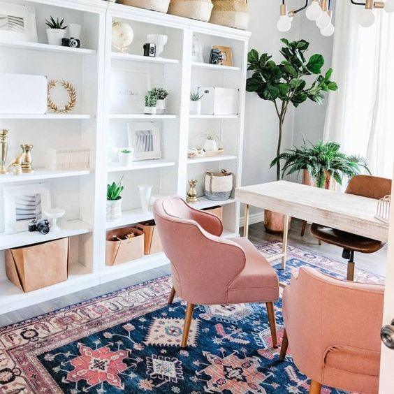 a bright girlish home office with a wooden desk, pink chairs, an open storage unit and a bright printed rug