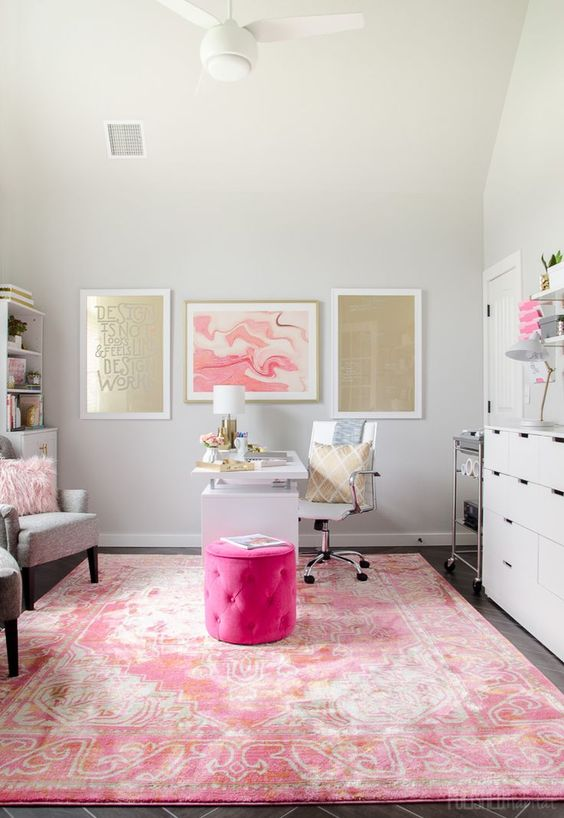 a bright home office with a hot pink ottoman, a pink rug and a gold and pink gallery wall