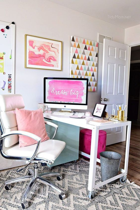a bright home office with a white desk and chair, a pink pillows and a colorful gallery wall plus a purple stool