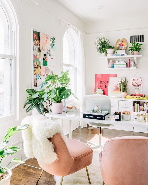 a bright home office with blush chairs, a colorful gallery wall, bright artworks and books and lots of greenery