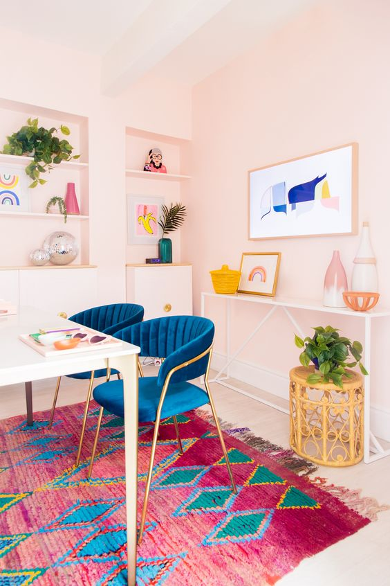 a bright home office with light pink walls, navy chairs, a colorful gallery wall and a rug, potted greenery