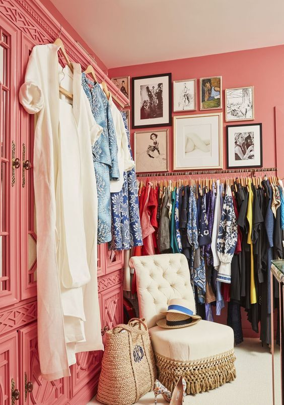 a bright pink feminine closet with wardrobes with mirror doors, a gallery wall, a makeshift closet and a beautiful neutral chair