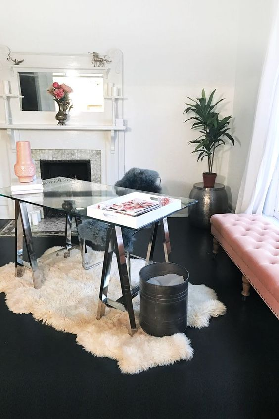 a catchy feminine home office with a glass trestle desk, a white fur rug, a tile clad fireplace and a blush daybed