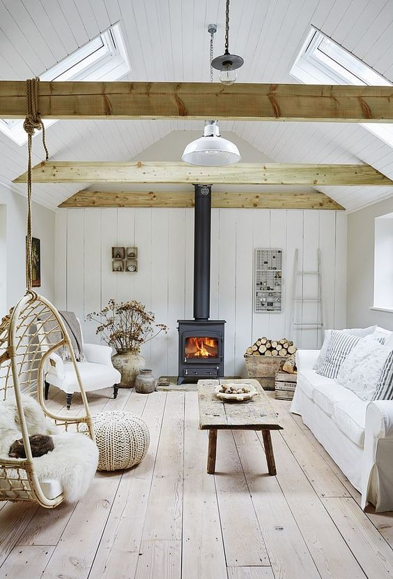a coastal barn living room in white, with wooden beams, a metal hearth, white seating furniture, reclaimed wood items and dried blooms
