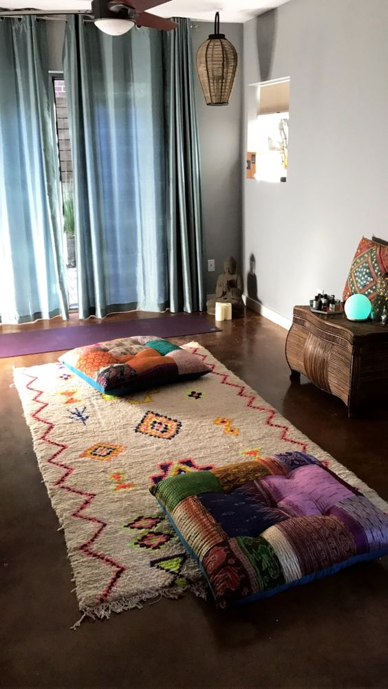 a colorful and boho meditation space with pillows, a colorful rug and wicker lamps