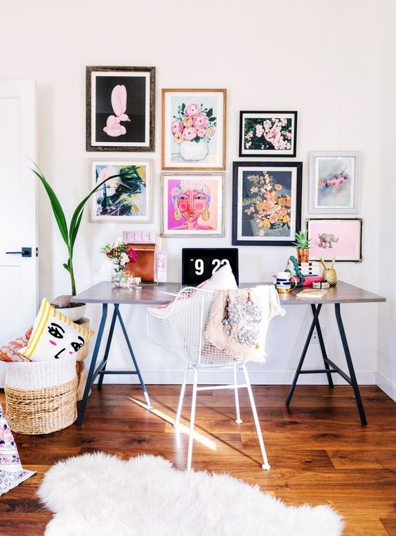 a colorful and fun girlish home office with a comfy desk, a bright gallery wall, a basket with pillows and a fur rug