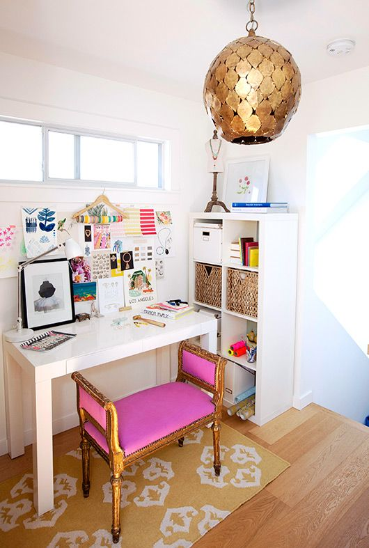 a colorful feminine home office with a hot pink stool, a gold scale pendant lamp and a bright gallery wall