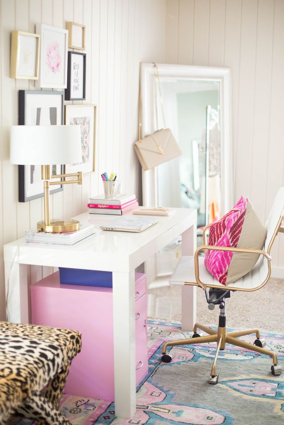 a colorful feminine home office with a white desk, a pink cabinet and pillow, a bright rug and a chic gallery wall