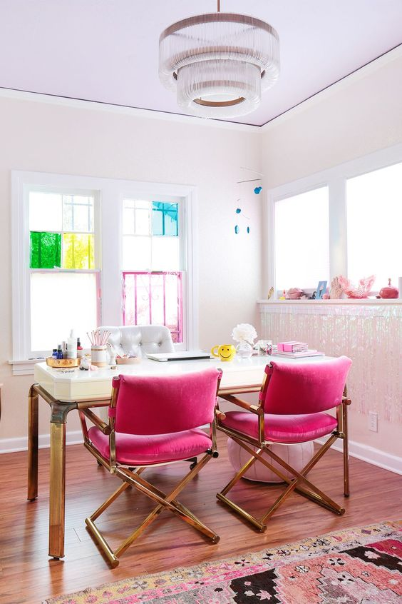 a colorful feminine home office with hot pink chairs, an elegant desk and bright touches