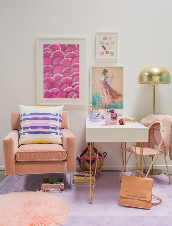 a colorful feminine space with a bright gallery wall, blush chairs and a rug and touches of gold for more chic
