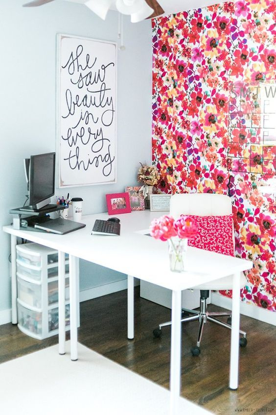 a colorful home office with a statement floral wall and a pillow and all white everything is bright and fun