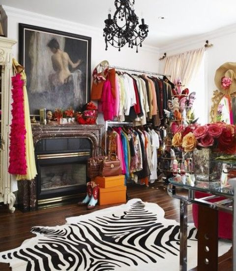 a colorful walk-in closet with open storage units, a fireplace, a zebra print rug, a black chandelier and a pretty glass vanity