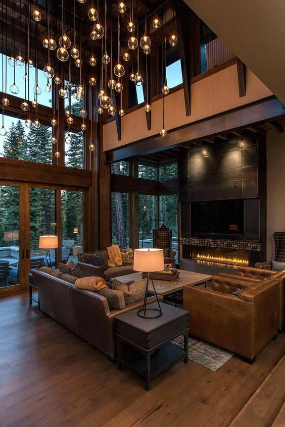 a contemporary barn living room with glazed walls, a built-in fireplace, an incredible chandelier with multiple bulbs, leather seating furniture and table lamps