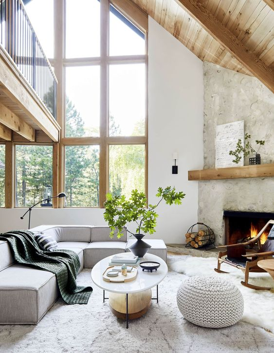 a contemporary living room with a fireplace clad with stone, a grey low sectional, an oval table, a crochet pouf, greenery branches and a floor lamp