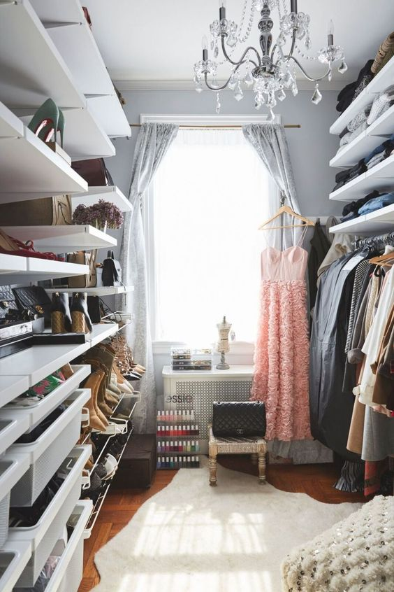 a cool grey closet with open shelves and racks, a bit of drawers, woven stools and a small vanity plus a crystal chandelier