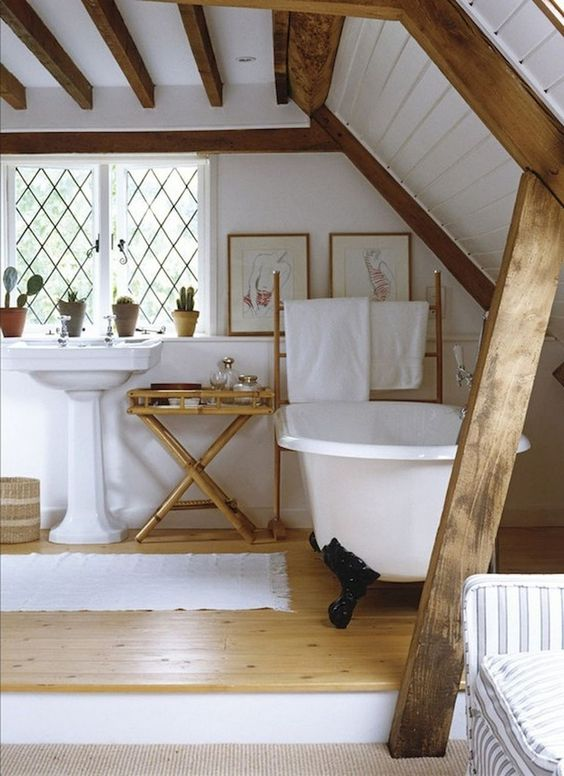 a cozy barn bathroom with white walls and a ceiling, stained wooden beams, a clawfoot tub and vintage furniture