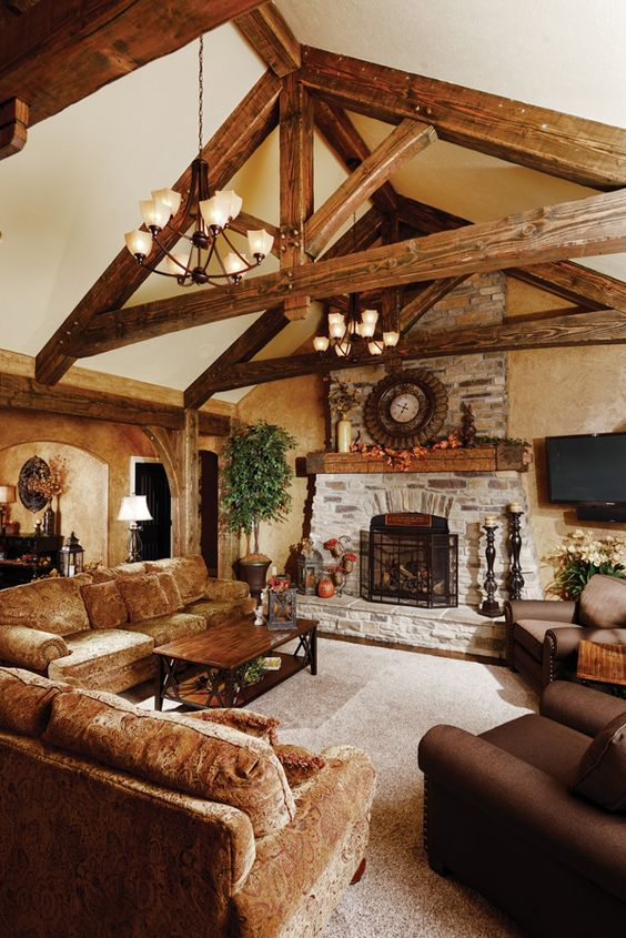 a cozy barn living room with neutral walls, wooden beams, a fireplace clad with stone, velvet and leather brown furniure and pendant chandeliers