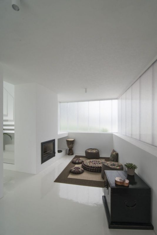 a cozy minimalist nook in white with a fireplace and a black chest plus cushions and pillows on the floor