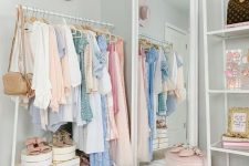 a cute pastel closet with light blue walls, an open makeshift closet, a large mirror, layered rugs, a pink stool and hats as decor