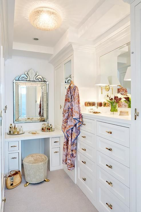 a delicate and chic small walk-in closet with white closed storage units and drawers, a white vnaity, a couple of mirrors and touches of gold