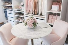 a delicate and subtle feminine closet with open shelves and storage units, pink chairs and a round stone table plus a crystal chandelier