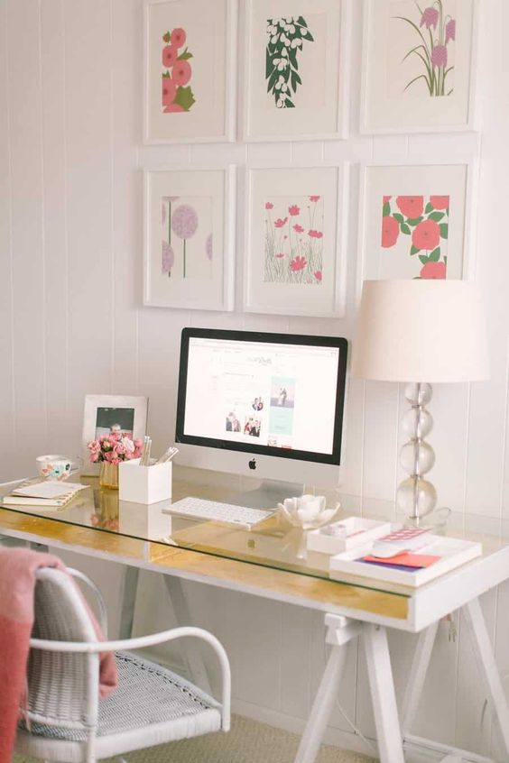 a feminine home office with a gold trestle desk, a white wicker chair and a colorful gallery wall plus touches of pink