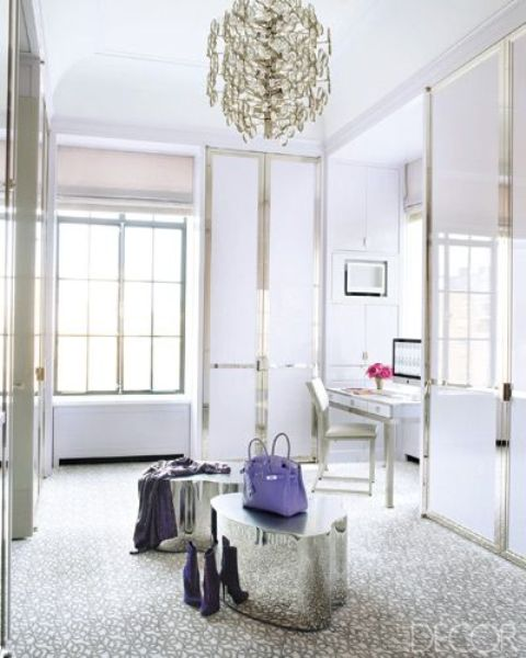 a glam and chic closet with wardrobes with sleek doors to keep it uncluttered, a bold chandelier and shiny stools