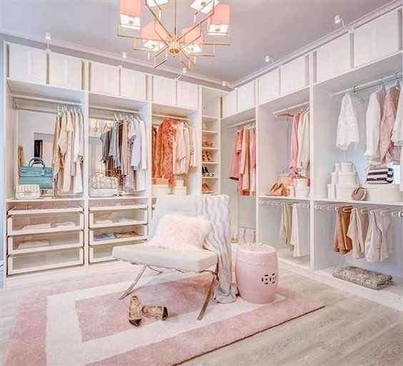 a glam feminine closet with open storage units, drawers, a pink chandelier, a chair and a side table plus a pink printed rug