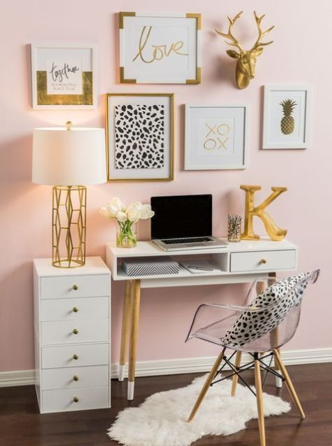 a glam feminine home office with a blush accent wall, white furniture, a glam gallery wall and lots of gold