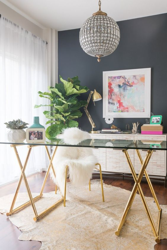 a glam feminine home office with a grey statement wall, a glass desk, a crystal chandelier and touches of gold