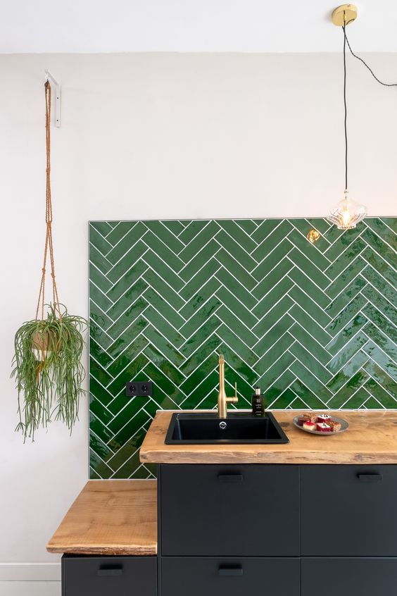 a graphite grey kitchen, butcherblock countertops and a bold green chevron tile backsplash for a lovely and bright look