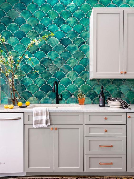 a grey kitchen with shaker cabinets, white stone countertops, a bold green fishscale tile backsplash and copper handles