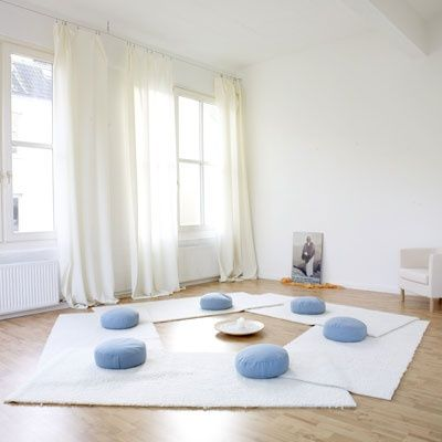 a home meditation room with white rugs and blue cushions and much light and air